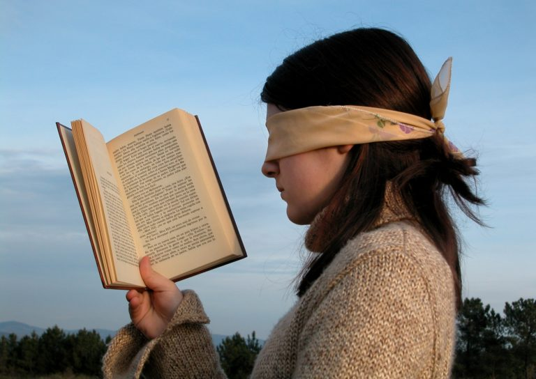 目隠しして本を読む女性