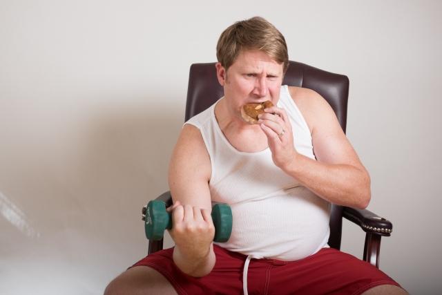 筋トレしながらドーナツを食べる男