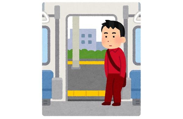 電車のドアの横に立つ人