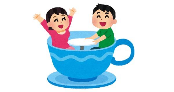 遊園地のコーヒーカップに乗るカップル